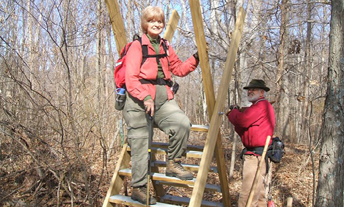 The HHC secretary and former HHC president build a hiking stile over a fence.